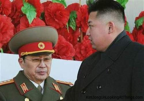 kim jong un looking at flowers behind man