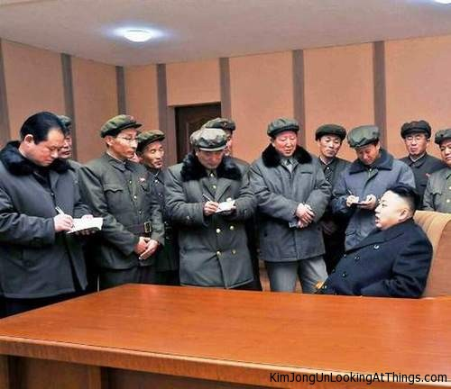 kim jong un looking at people taking notes